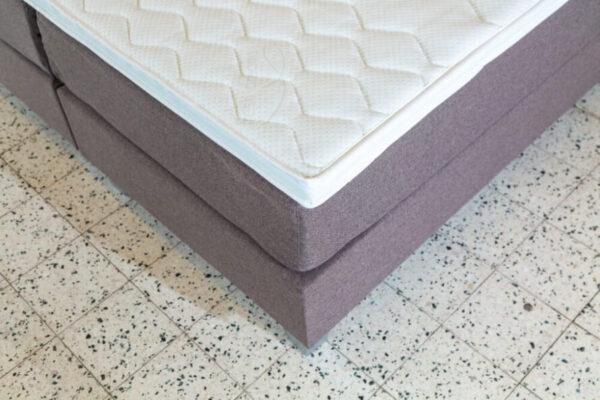 hoek van vlak boxspring bed in de kleur taupe met wit topmatras