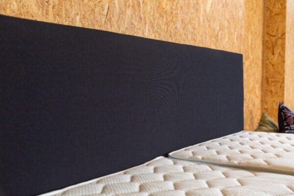 zwart bed hoofdbord met een houten achtergrond
