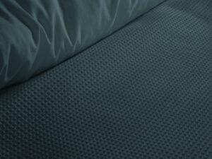 detail van een donkergroen dekbedovertrek met wafelpatroon