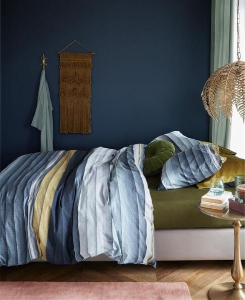 bed opgedekt met een gestreept dekbedovertrek van het merk At Home