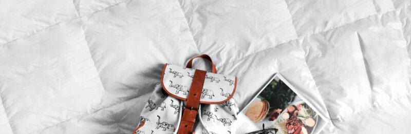 wit dekbed met daarop een tas en magazine