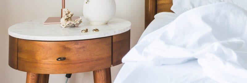 banner met daarop een houten nachtkastje afgebeeld en een deel van een bed