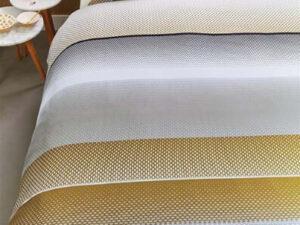opgedekte boxspring met dekbedovertrek Tibbe in de kleuren grijs goud en wit