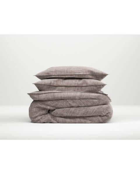 dekbed en hoofdkussens opgestapeld met een bruine dekbedovertrek van Zo! Home