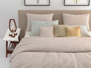 detail van opgemaakt bed met daarop een beige dekbedovertrek