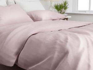 bed opgedekt met katoen-satijn dekbedovertrek in de kleur licht roze shady pink