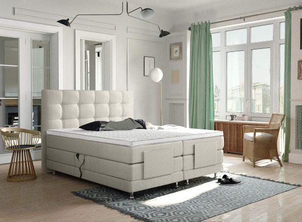 beige boxspring elektrisch opgesteld in een slaapkamer met witte topper
